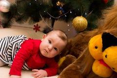 En mycket liten flicka sitter under en julgran med färgrika garneringar nytt treeår för jul Arkivbild
