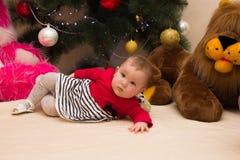 En mycket liten flicka sitter under en julgran med färgrika garneringar nytt treeår för jul Royaltyfri Foto