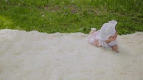 En mycket liten och härlig flicka som spelar på överkastet i, parkerar stock video