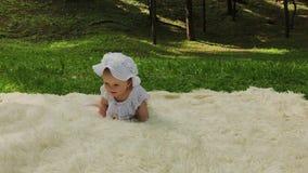 En mycket liten och härlig flicka som spelar på överkastet i, parkerar arkivfilmer