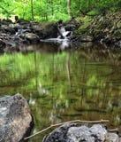 En mycket liten skogsmarkvattenfall matar ett litet damm Royaltyfria Foton