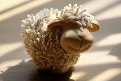En mycket liten souvenir av får som garnering Arkivfoton