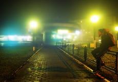 En mystisk man står bara i gatan, bland bilar i en tom stad, går nattgatan, drömmer Arkivbild