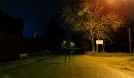 En mystisk man står bara i gatan, bland bilar i en tom stad, weatvägen, efter regnet, har gått nattgatan, drömmer Royaltyfri Fotografi