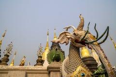 En mytisk varelse med elefant-som huvudet framme av gruppen av pagoder i en buddistisk tempel i Thailand fotografering för bildbyråer