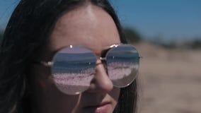 En nära sikt av en härlig flicka som sätter på solglasögon Havsvågor reflekterar i skuggorna lager videofilmer