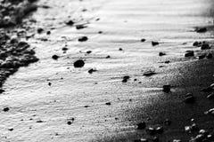 En nära sikt av vatten på en sjökust, med detaljer av sander och små runda stenar arkivbilder