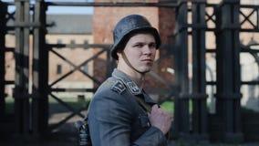 En nära stående av en ung tysk soldat med ett gevär som ser rakt, vänder hans huvud till rätten och ser lager videofilmer