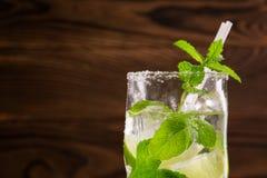 En närbild av en mojitococtail på en träbakgrund Grön mintkaramell och ny limefruktmojito Uppfriskande alkoholdrinkar kopiera avs Fotografering för Bildbyråer