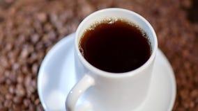 En närbild av ett vitt keramiskt rånar fyllt med kaffe på en hög av bönor stock video