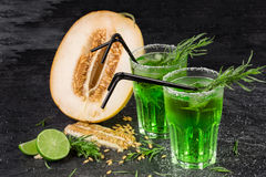 En närbild av exotiska frukter Gröna alkoholcoctailar med sugrör klipp melonen Dragondrings och ny limefrukt på en svart bakgrund arkivbild