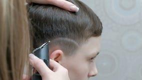 En närbild av händerna av en frisör som rakar bilden på huvudet av en ung man med en elektrisk clipper En tonåring in stock video