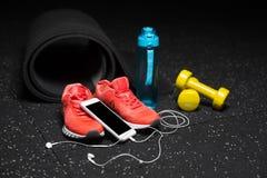 En närbild av idrottshalltillbehör för sportutbildning Dum-klockor, flaska och sportskor med en smart telefon på ett golv Royaltyfri Bild
