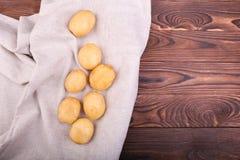 En närbild av nya och nya potatisar sprids på ett grått tyg på en trätabell för mörk brunt, bästa sikt åkerbruka produktgrönsaker Royaltyfria Foton