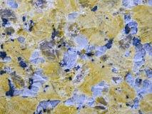 En närbild av en textur av en polerad gul granitstenyttersida Royaltyfri Foto