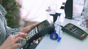 En närbild av en ultrarapidbild av betalningen av en kreditkort Säljaren skriver in beloppet på terminalen, stock video
