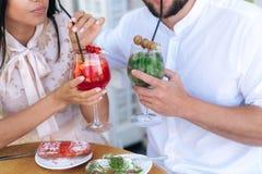 En närbild, en obscen ram, en man och en kvinna i ett kafé, drar ljusa exponeringsglas med bärcoctailar, tycker om smakliga frukt Royaltyfri Fotografi