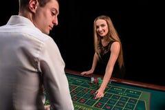 En närbild på baksidan av croupier i en vit skjorta, bilden av den gröna kasinotabellen med rouletten och chiper, rich arkivfoton