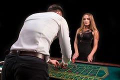 En närbild på baksidan av croupier i en vit skjorta, bilden av den gröna kasinotabellen med rouletten och chiper, rich arkivbild