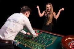 En närbild på baksidan av croupier i en vit skjorta, bilden av den gröna kasinotabellen med rouletten och chiper, rich arkivbilder