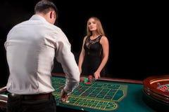 En närbild på baksidan av croupier i en vit skjorta, bilden av den gröna kasinotabellen med rouletten och chiper, rich royaltyfria bilder