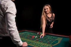 En närbild på baksidan av croupier i en vit skjorta, bilden av den gröna kasinotabellen med rouletten och chiper, rich fotografering för bildbyråer