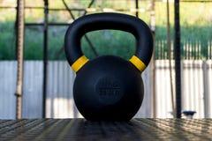 En närbild på en svart sexton kg vikt med gul stri royaltyfria foton