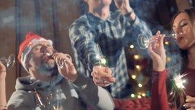 En närbild sköt på folk som firar jul med vin och tomtebloss stock video
