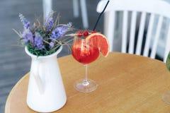 En närbildbär-citrus coctail står i ett exponeringsglas på en tabell bredvid en dekorativ vas av vildblommor Inre Royaltyfria Foton