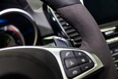 En närbildsikt av en del av inre av en modern lyxig bil med en sikt av växelspakskovlarna som göras av krom med fotografering för bildbyråer