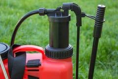 En närbildsprejare för växtbekämpningsmedel, röd sprejare för jordbruk på en grön bakgrund arkivfoton