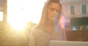 En närbildstående av ett kvinnligt arbete på hennes bärbar dator, som kameran flyttar upp och fångar solblicks lager videofilmer