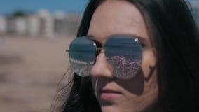 En närbildstående av en härlig flicka i solglasögon på stranden Havet med vågor reflekterar i solglasögon arkivfilmer