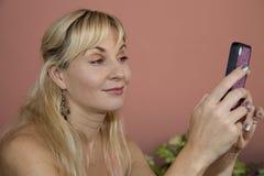En nätt blond kvinna som smsar på hennes rosa mobiltelefon arkivfoton