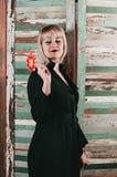 En nätt blondin i den svarta klänningen som rymmer en pinne av den röda godisen royaltyfria bilder