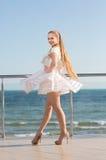En nätt dam som går på en terrass En le kvinnlig på en ljus himmelbakgrund En stilfull flicka i en kort vit klänning nära ett hav Royaltyfri Foto
