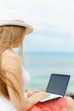 En nätt europeisk kvinna är sittinen på en kust för sten nästan av det tropiska havet och att skriva något idé, brev eller jobb f arkivbilder