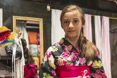 En nätt flicka i en kimono Kimonot är det slitna populärt för traditionell klänning i Japan Europeisk flicka i kimono arkivbild