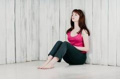 En nätt flicka i en rosa överkant och att sitta på golvet som lutar på wa royaltyfri foto