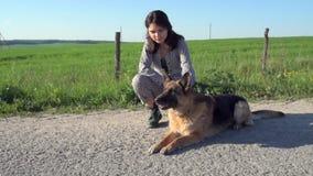 En nätt flicka leder en hund bredvid henne på vägen lager videofilmer
