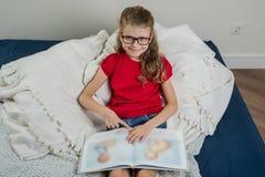 En nätt flicka med exponeringsglas, en grundskolastudentläsning Arkivfoto