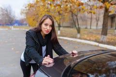 En nätt flicka och en svart bil arkivfoto