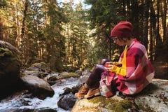 En nätt hipsterflicka med en plädpläd på hennes skuldror i en hatt och en gul tröja och exponeringsglas med en råna av kaffe Arkivfoto