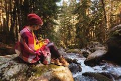 En nätt hipsterflicka med en plädpläd på hennes skuldror i en hatt och en gul tröja och exponeringsglas med en råna av kaffe Arkivfoton