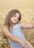 En nätt lycklig flicka som rymmer händerna för moder` s i guld- vetefält Begrepp av renhet, tillväxt, lycka royaltyfria bilder