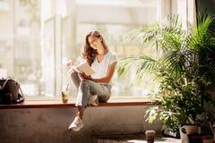 En nätt slank ung flicka med långt hår, bärande tillfällig dräkt, sitter på fönsterbrädan och läser en bok i ett hemtrevligt kafé arkivbilder