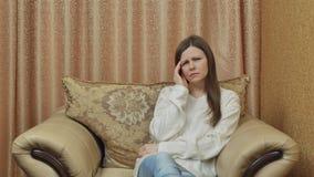 En nätt ung flicka rymmer hennes händer bak hennes huvud och lider från migrän En härlig kvinna från fördjupning lager videofilmer