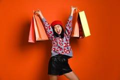 En nätt ung kvinna som stylishly är iklädd en hatt med påsar, når att ha shoppat royaltyfria foton
