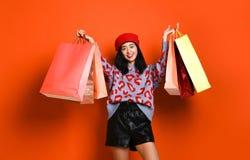 En nätt ung kvinna som stylishly är iklädd en hatt med påsar, når att ha shoppat royaltyfria bilder