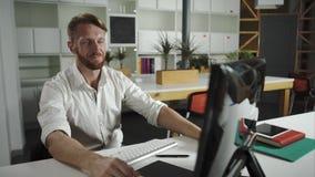 En nöjd affärsmansittingin hans kontor som arbetar på hans dator